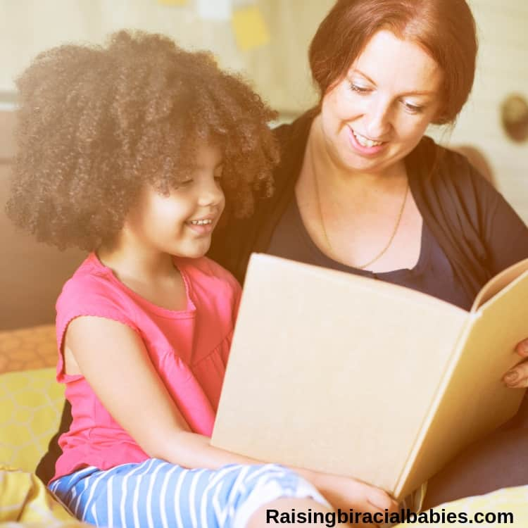 Caucasian mom reading a book to biracial daughter