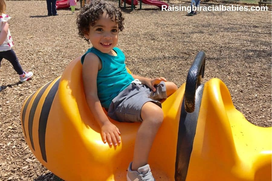 little mixed race boy on the playground in the summer