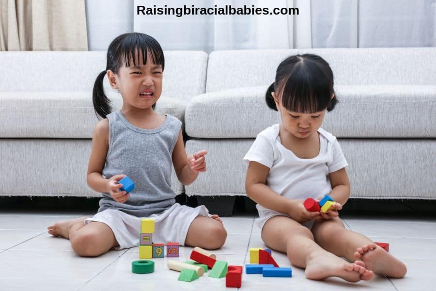 two toddler girls playing with blocks. One girl is crying because the other isn't sharing.