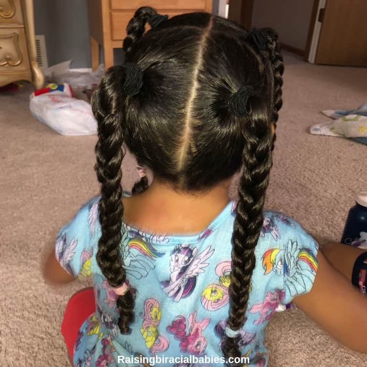 Little mixed girl facing away from the camera so you can see her sleek braided hairstyle.