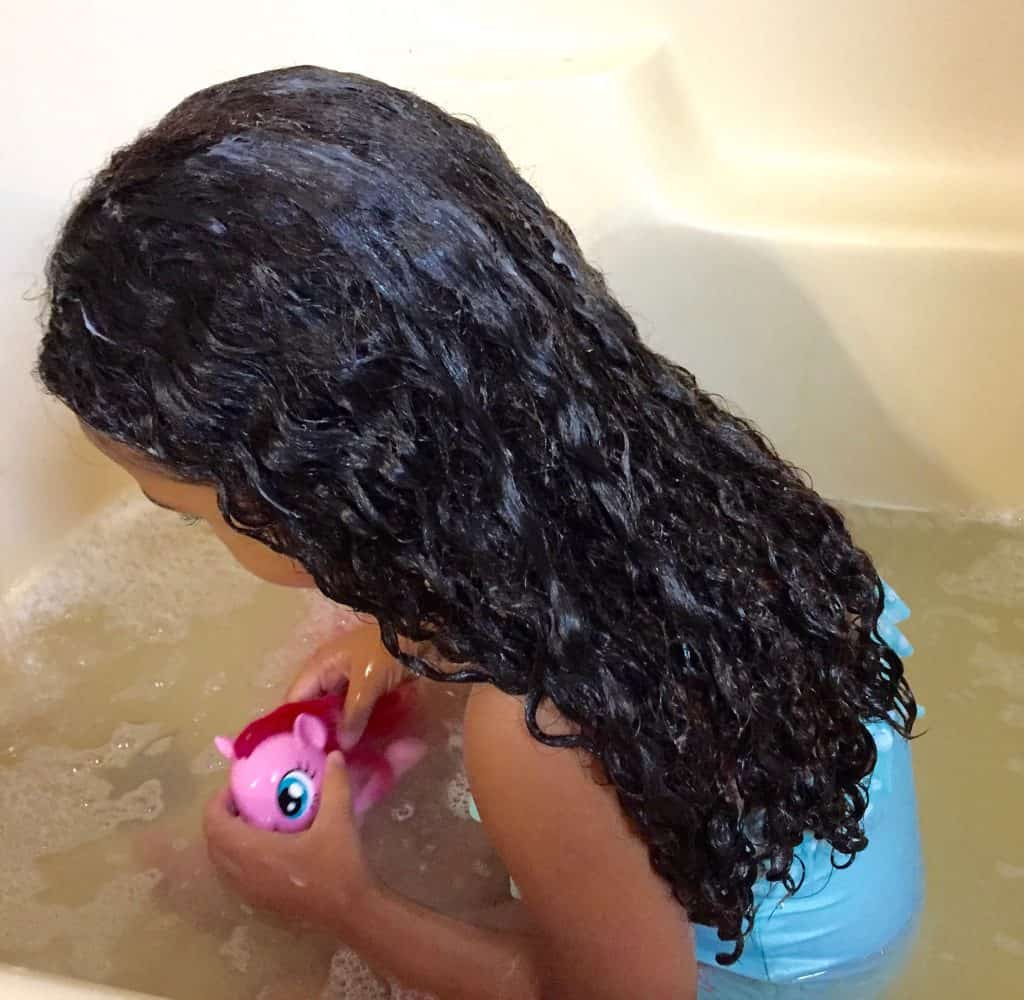 little mixed girl in the tub with a bathing suit on, facing away from the camera with wet curly hair.
