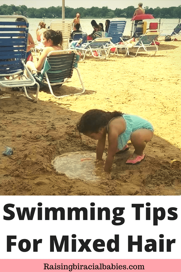 a little mixed girl playing in the sand and water at the beach with text overlay that says swimming tips for mixed hair.