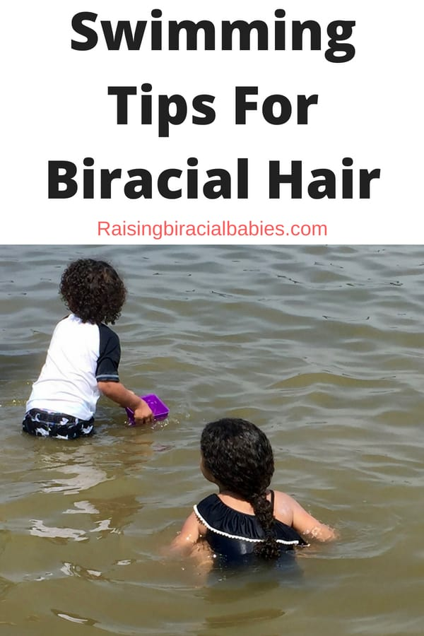two little kids playing in the water at the beach, facing away from the camera, with text overlay that says swimming tips for biracial hair.