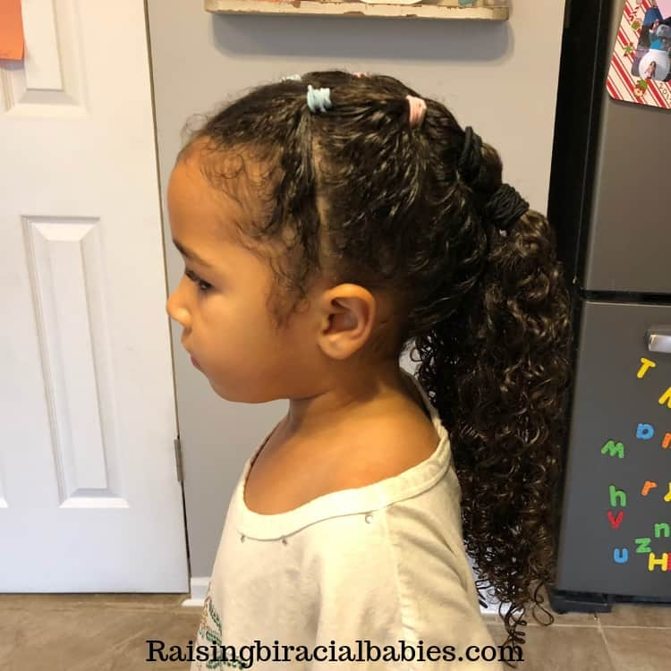 a versatile mixed girls hairstyle. Half ponytail, pigtail with curly hair at the bottom