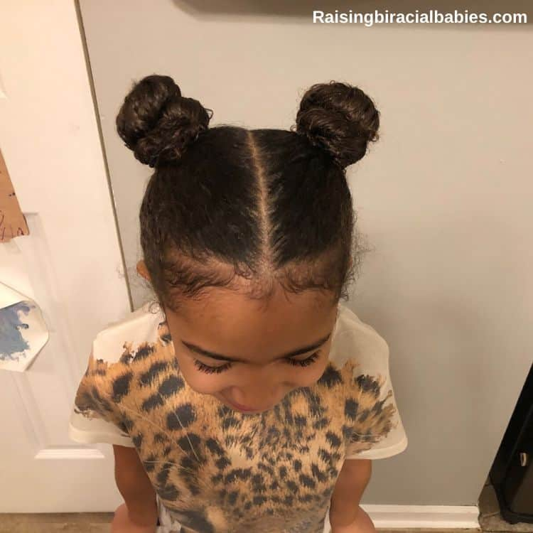 a little girl with double top knot buns showing an easy hairstyle for mixed race hair
