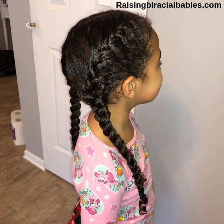 little girl facing the wall with a side view of her mixed hair in french braid pigtails.