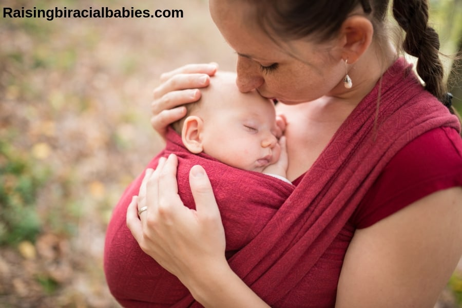 Mother babywearing her newborn baby in a red wrap.