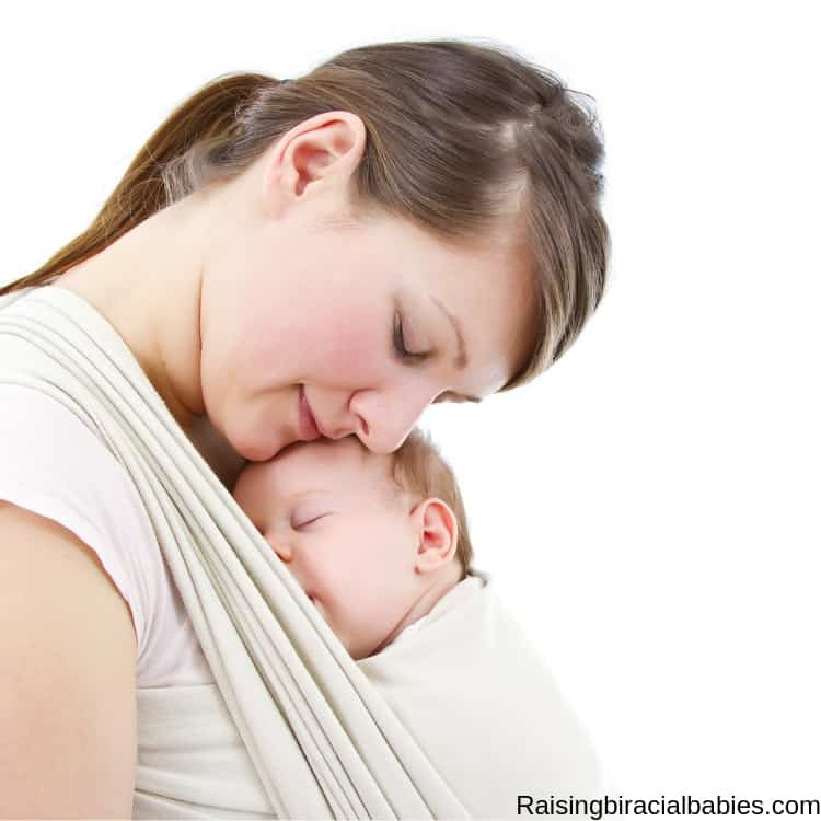 Mother babywearing her newborn in a wrap