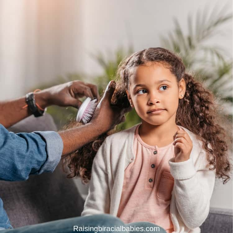 man brushing little girl's dry, curly hair