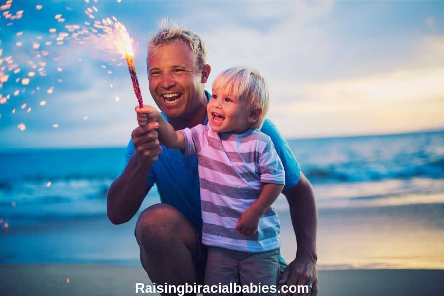 dad showing toddler son how to safely hold a sparkler for the 4th of july