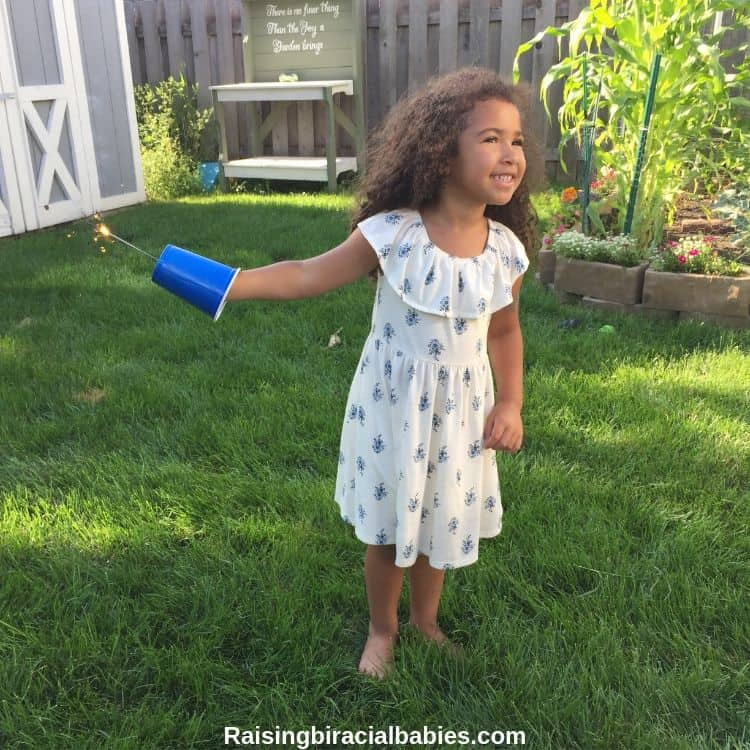 little girl safely holding a sparkler in a cup for the 4th of july