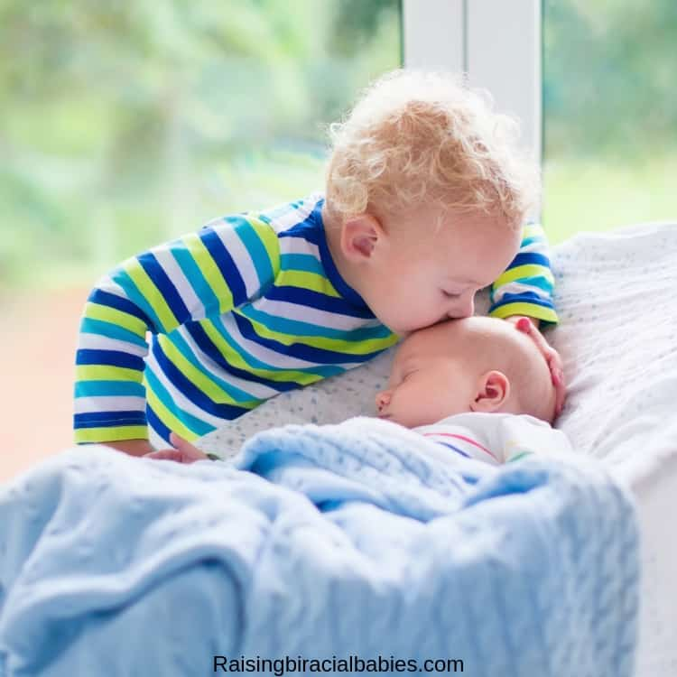 a toddler boy kissing his newborn baby brother on the head