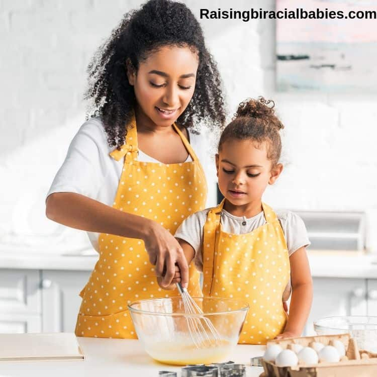 mom and young daughter in the kitchen mixing ingredients together to bake something