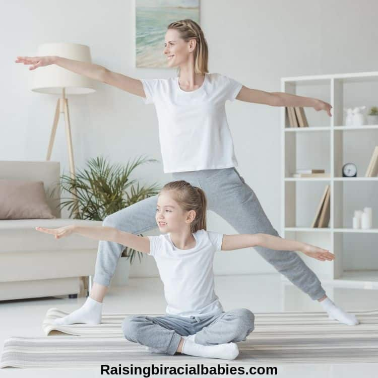 mom and young daughter doing yoga inside their house