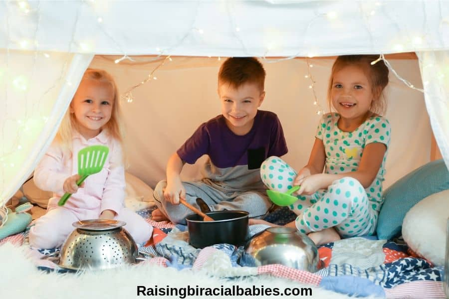 three little kids laughing inside a fort using kitchenware and pots as instruments.
