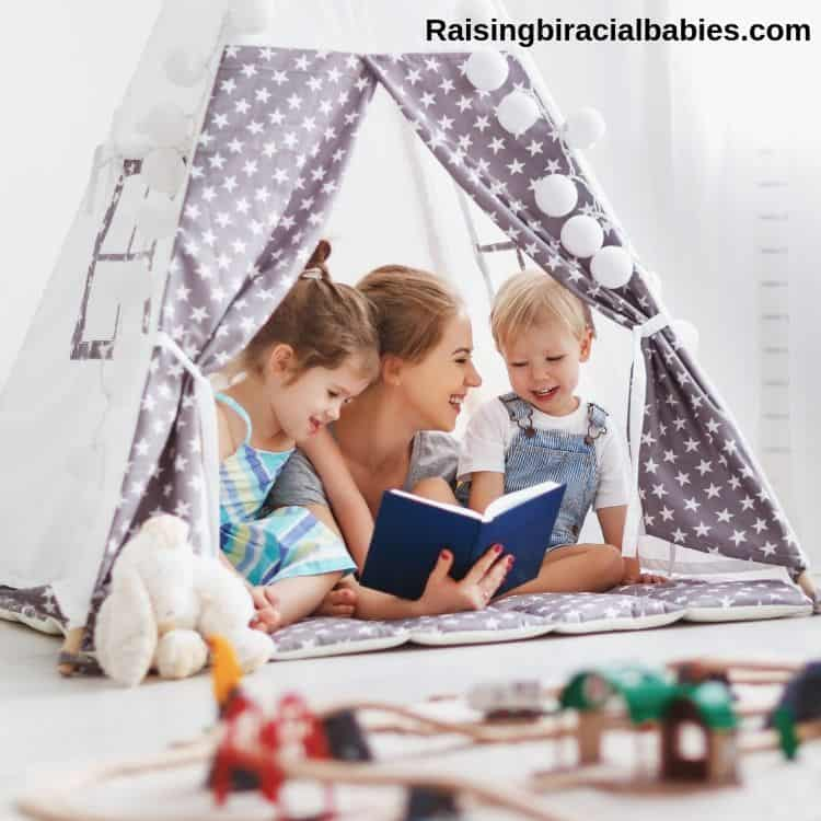 mom and two little kids inside an indoor tent reading a book together and laughing