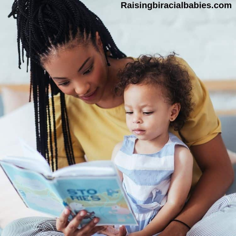 mom reading a book to her toddler daughter who is sitting in her lap