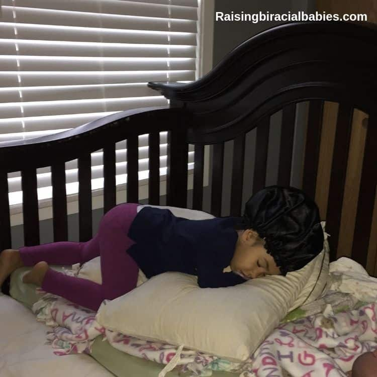 little girl sleeping with a satin cap on to protect her curly mixed hair.