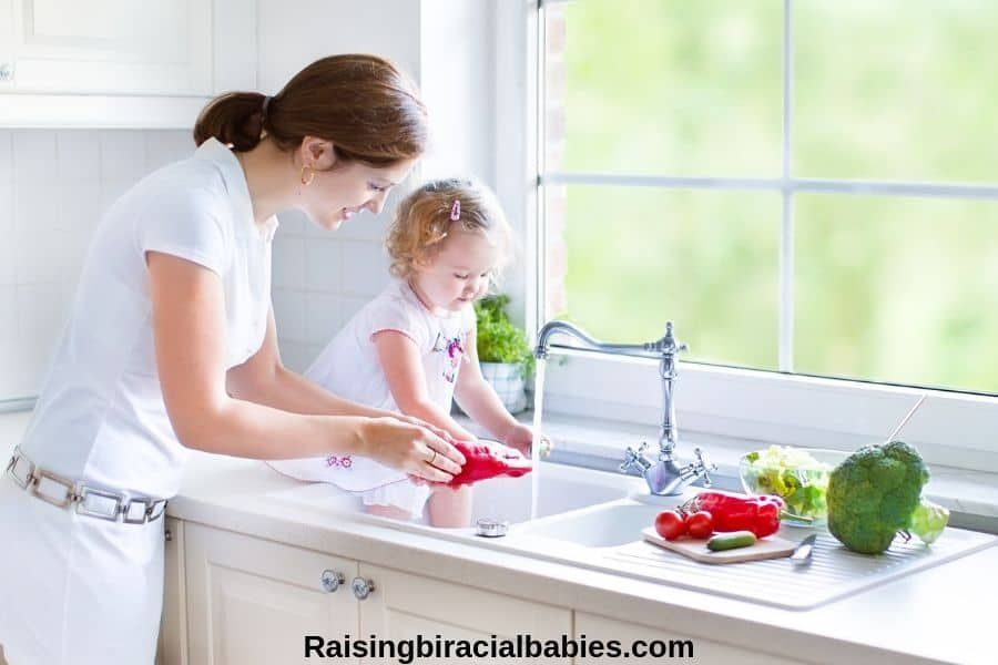 mother and toddler daughter in the kitchen washing vegetables in the sink
