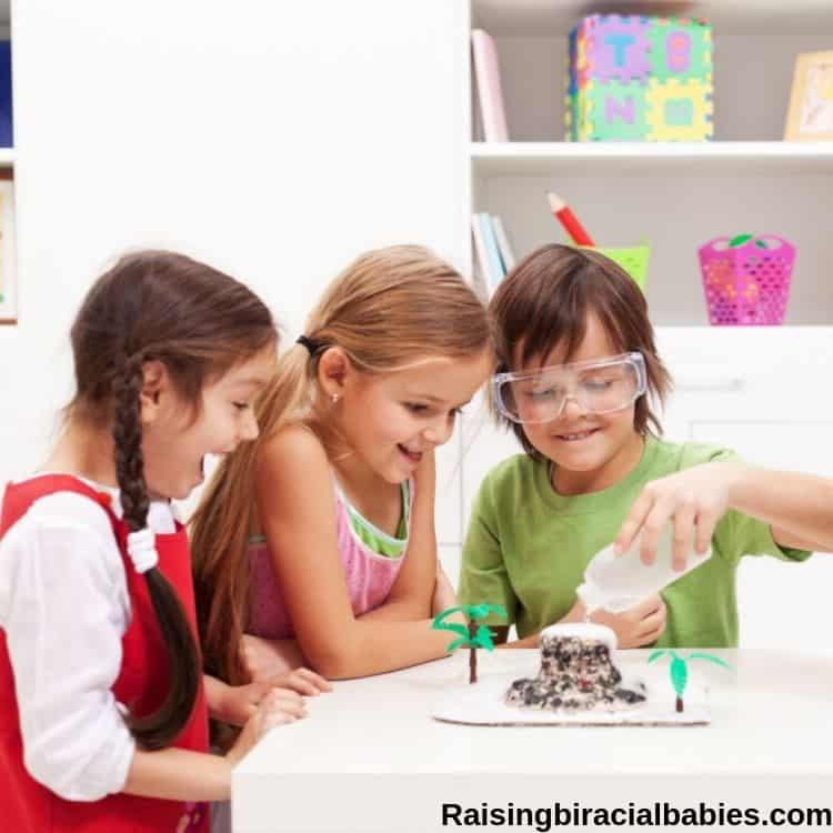three children gathered around a table as one of them is making a homemade erupting volcano.