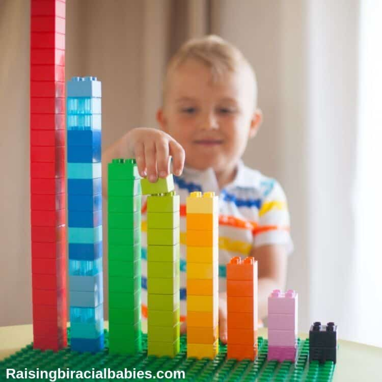 a little boy stacking lego blocks by color and from tallest to shortest.