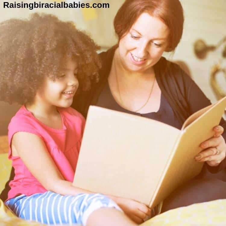 a mom reading a book to her young daughter.