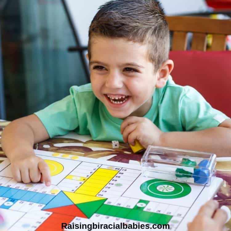 a little boy laughing and playing a board game