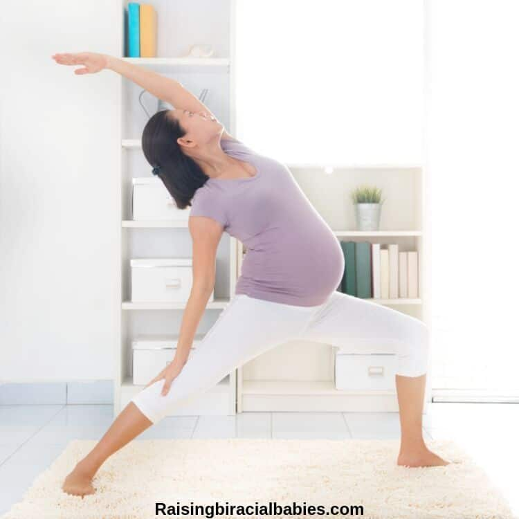 a pregnant woman doing a yoga exercise in her home