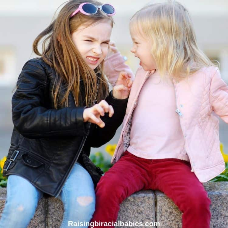 two little sisters fighting with each other. One has her hands out in a claw-like position and the other sister is angry and pulling the older sisters hair.