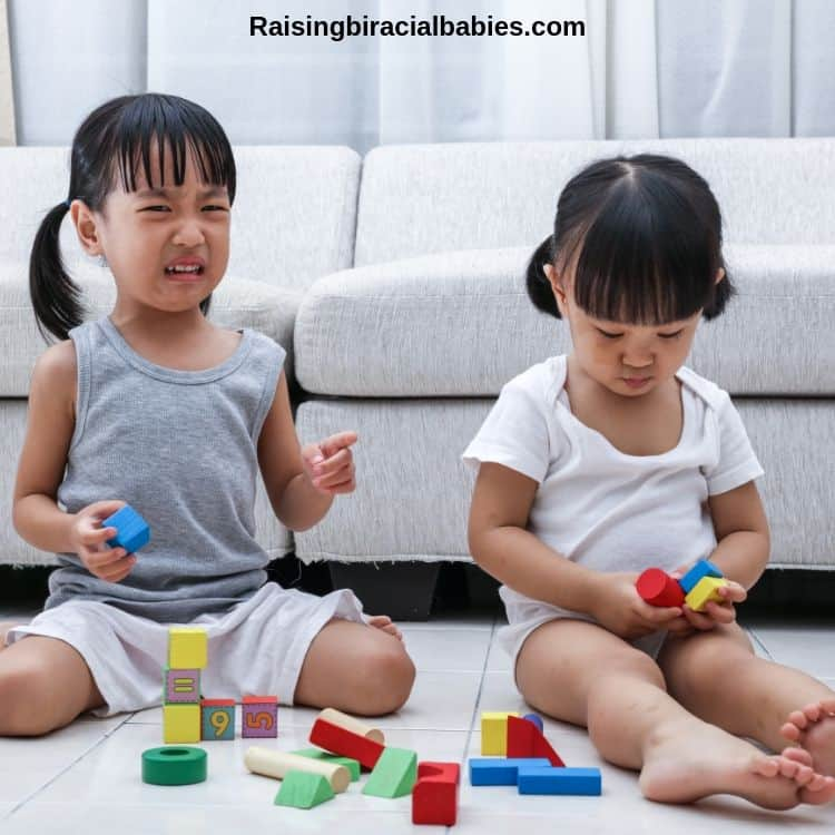 two toddler sisters playing with blocks. One girl is crying because the other isn't sharing.