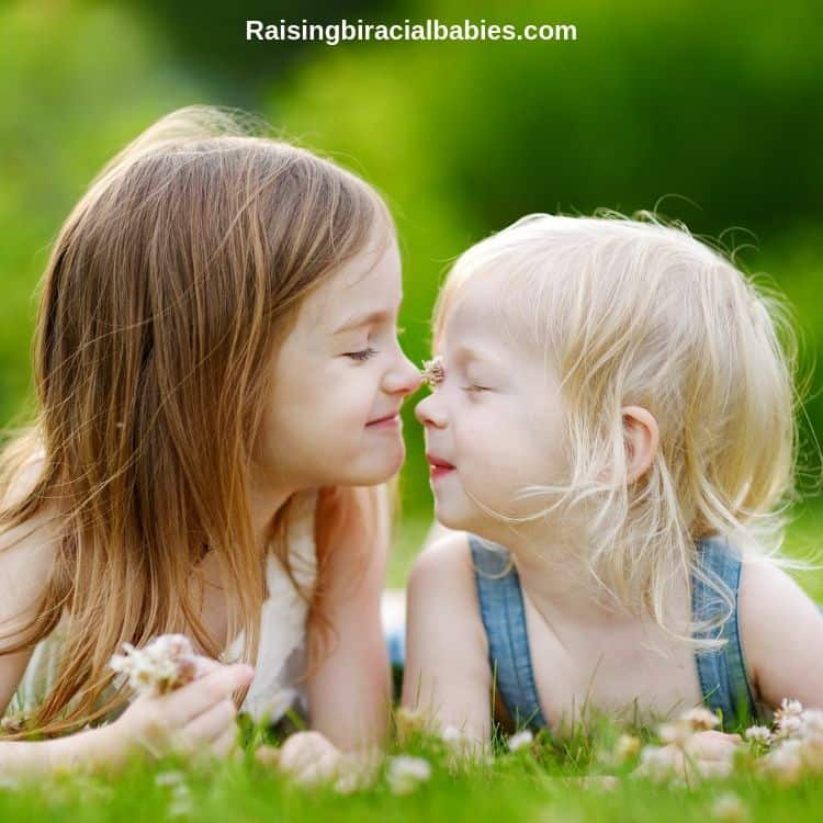 two young sisters smiling at each other and touching noses.