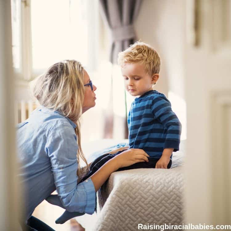 a mom talking with her toddler son in a bedroom. He's sitting on the bed and she's kneeling in front of him.
