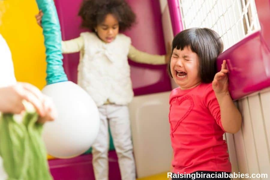 A toddler girl having a tantrum in a play area with a child in the background