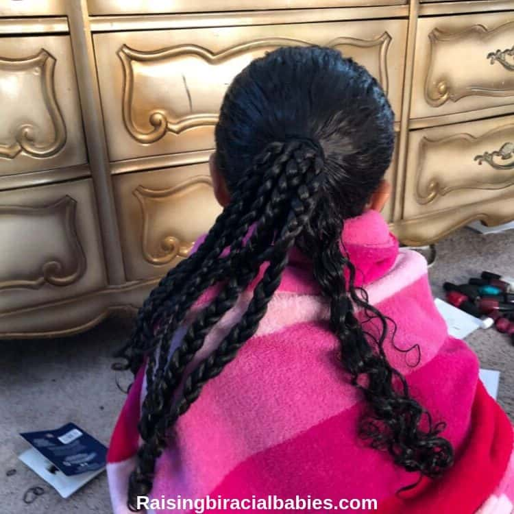 The back of a little girls head showing the progression of a hairstyle. It's in a ponytail with several small braids on the left side and some loose curly hair on the right side.