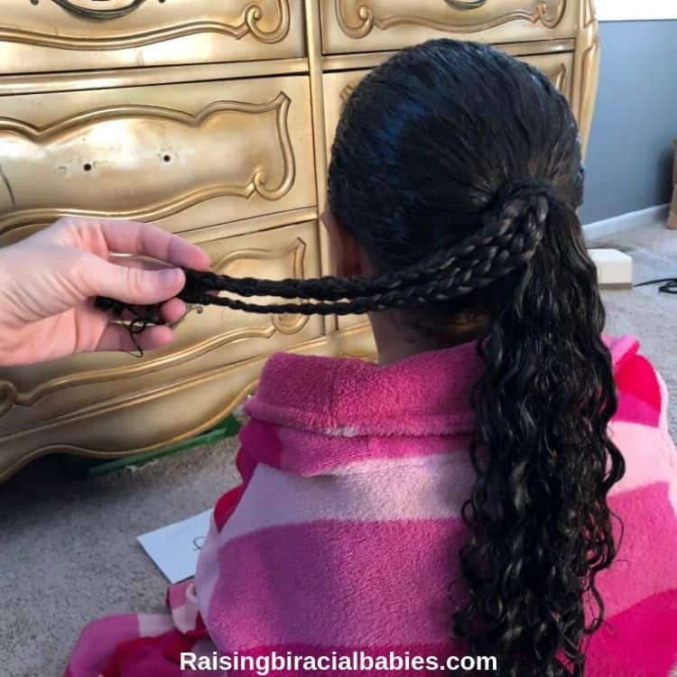 The back of a little girls head. Her hair is in a ponytail and her mom is holding a few small braids away from the rest of the ponytail.