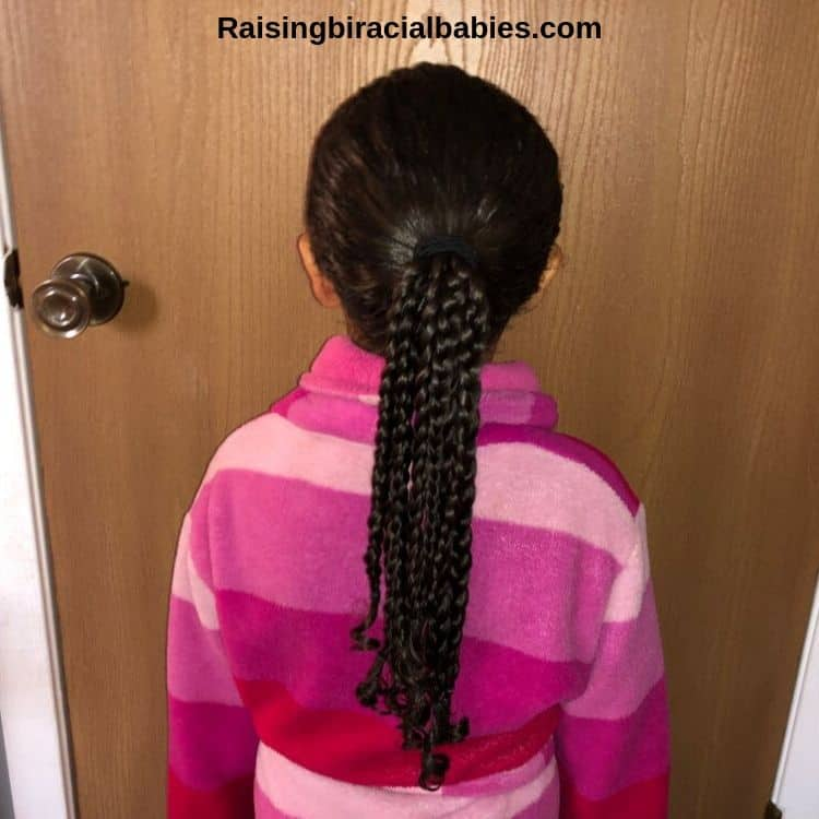 The back of a little girls head showing a ponytail with a bunch of braids.
