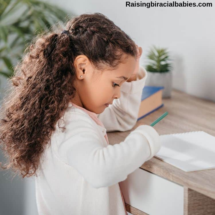a little girl with fine curly mixed hair sitting at a desk writing on a paper.