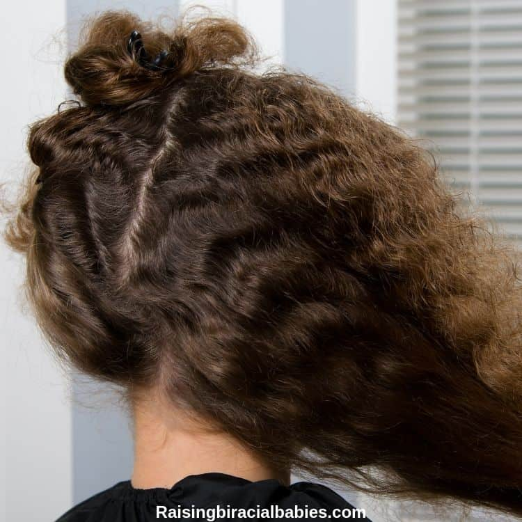 a mixed girls long curly hair parted in the back. One side is clipped up and the other is pulled to the side as if it's being sectioned.