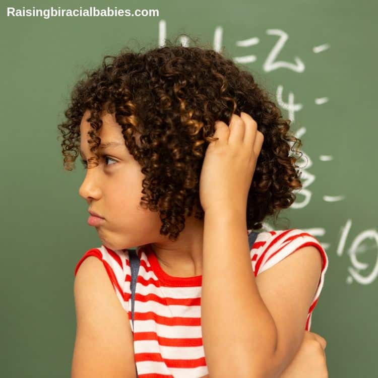a mixed boy with very curly hair standing in front of a chalkboard looking to the side, scratching his head.