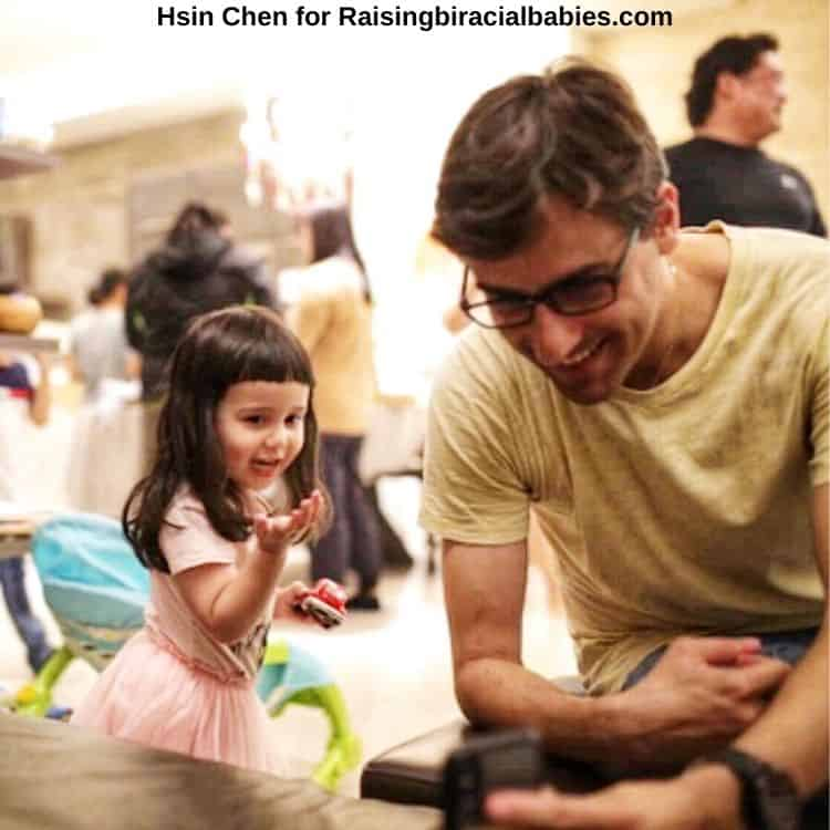 a dad with his biracial daughter looking at a phone