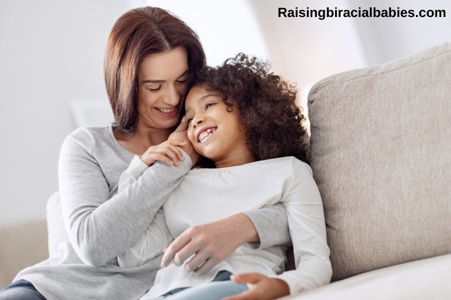 a white mother and her biracial daughter cuddling and smiling on the couch