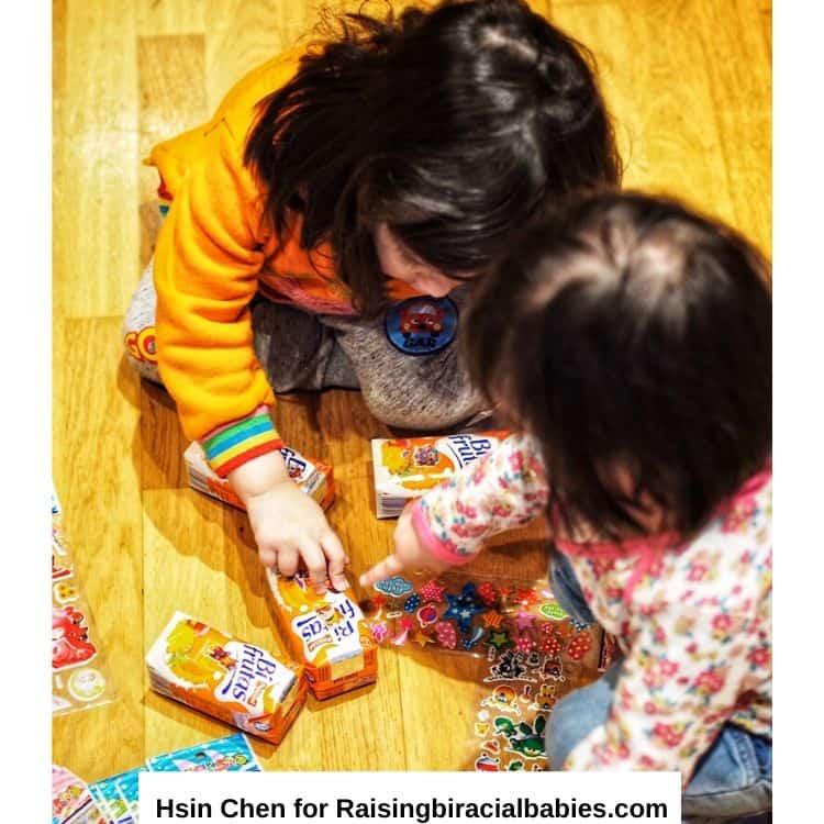 two little girls doing an activity together on the floor