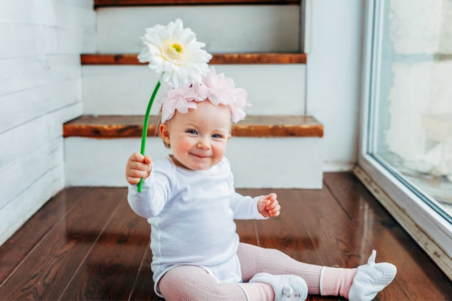 baby girl smiling and holding a flower