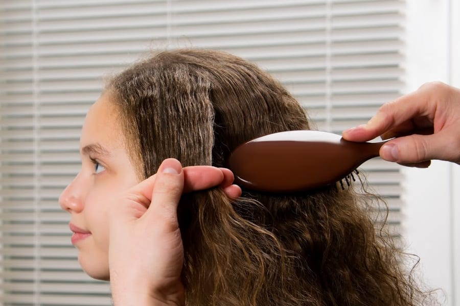 side view of a biracial girl getting her hair brushed
