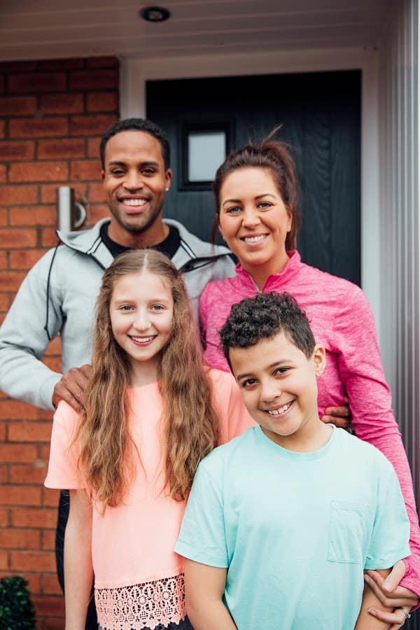 an interracial family standing at their door smiling