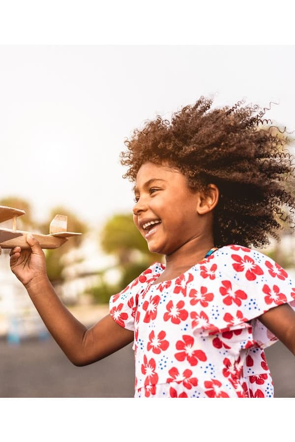 biracial girl holding a wooden airplane smiling