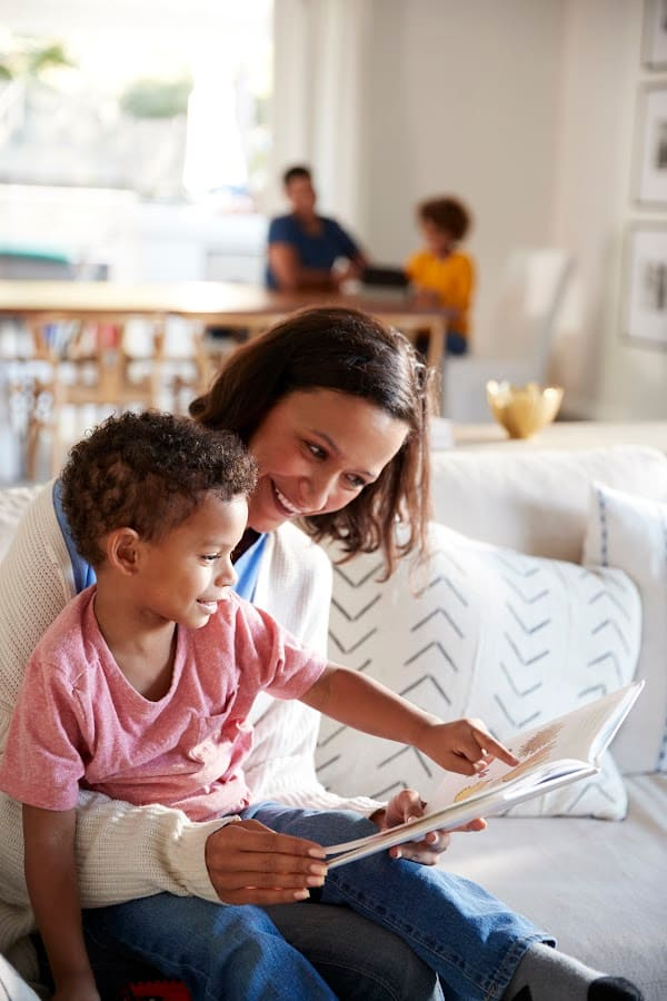 white mother with biracial son looking at a book together on the couch